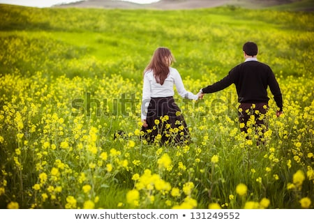Anonymous woman with flowers walking in field Stock photo © dashapetrenko