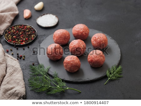 Fresh raw minced beef meatballs on round board with pepper, salt and garlic on black background. Stock photo © DenisMArt