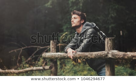 young man leaning on a wooden fence stock photo © photography33