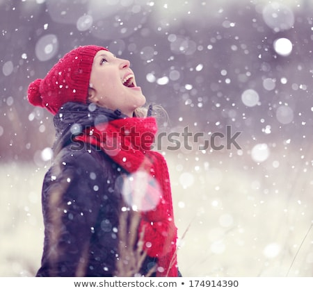 smiling young woman in falling snow Stock photo © artjazz