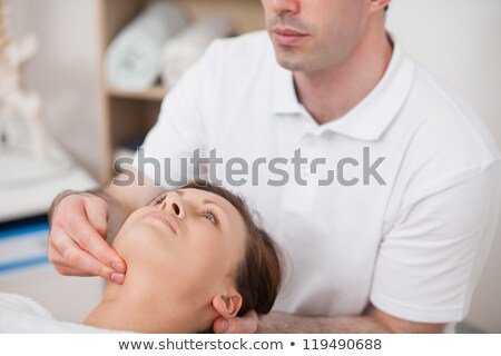 Close-up of doctor pressing two fingers on the neck of his patient indoors stock photo © wavebreak_media