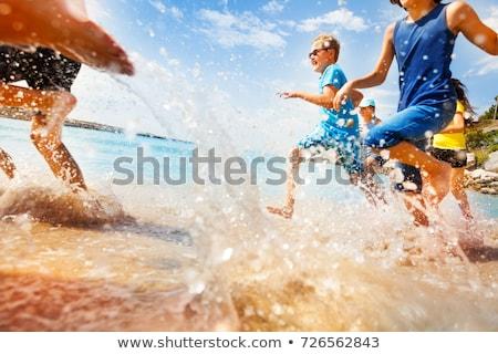 Jóképű tini jókedv úszik óceán tengerpart Stock fotó © meinzahn