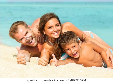 family with son lying on sand with hands up stock photo © paha_l
