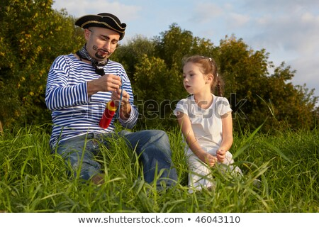Dad in pirate suit and daughter is sitting on grass. dad get ready to inflate air-balloon Stock photo © Paha_L