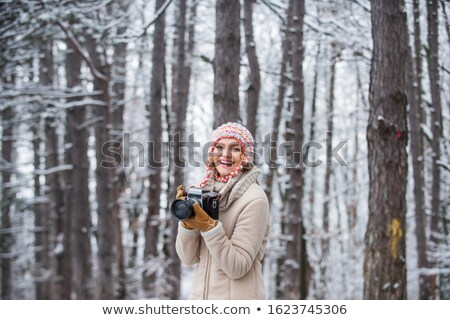 pretty woman photographer taking photos at winter forest in mountains stock photo © deandrobot