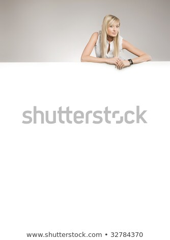 Stock photo: Attractive blonde over white empty board, lots of copyspace