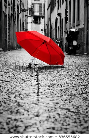 red umbrella on cobblestone street in the old town wind and rain stock photo © photocreo