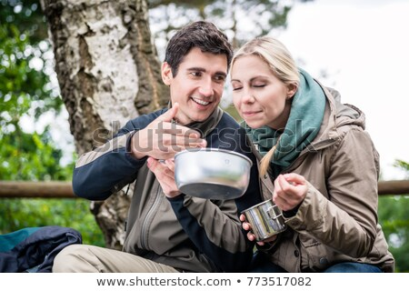 Backpacker during hike eating out of tin bowl Stock photo © Kzenon
