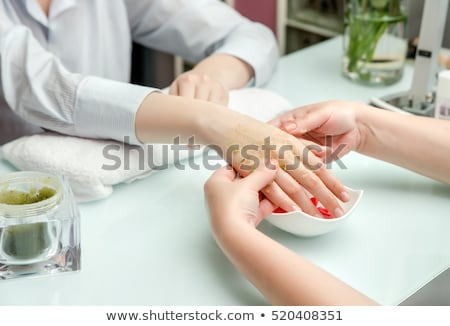 Stock photo: Woman in nail salon receiving pedicure by beautician