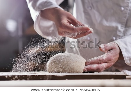 chef hands preparing dough on table at kitchen stock photo © dolgachov