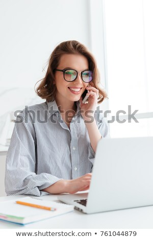 Elegant smiling woman in glasses and striped shirt using laptop  Stock photo © deandrobot