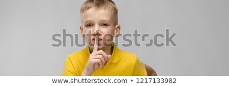 Portrait of cute little blonde caucasian boy in yellow t-shirt showing shh sign on gray background Stock photo © Traimak