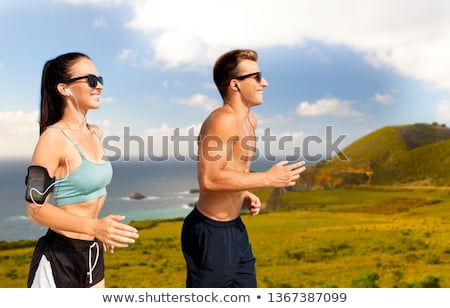 smiling couple running over big sur hills Stock photo © dolgachov