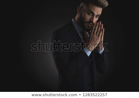portrait of young businessman in navy suit praying Stock photo © feedough