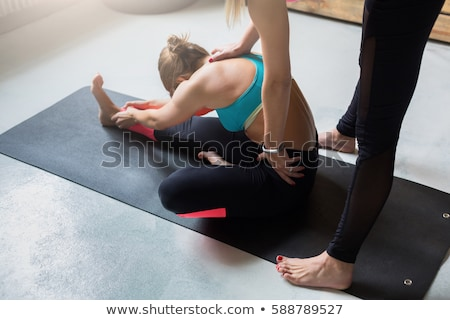 Instructor helps beginner to make yoga pose Stock photo © Kzenon