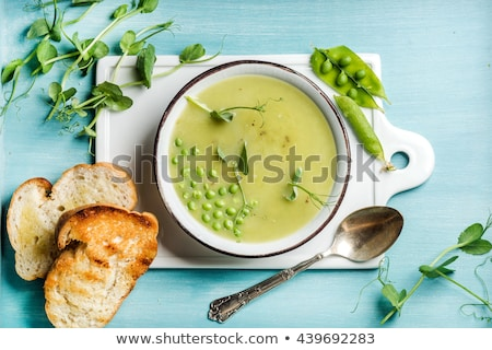 Creamy soup with green pea in a ceramic white plate Stock photo © dash