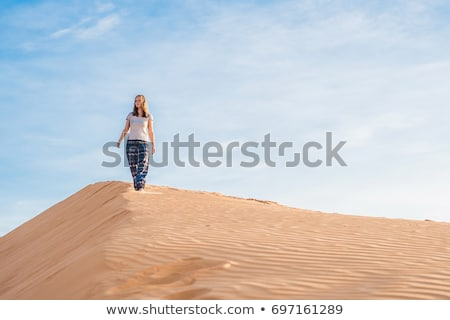 young woman in rad sandy desert at sunset stock photo © galitskaya