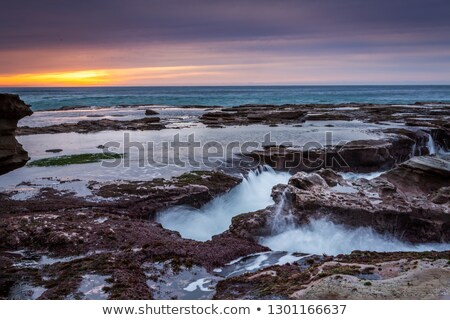 Ocean flowing into coastal channels eroded into rock and a stunning sunrise Stock photo © lovleah