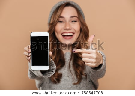 smiling curly woman in casual clothes showing blank smartphone screen stock photo © deandrobot