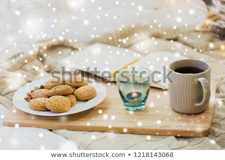 cookies tea and candle at home over snow stock photo © dolgachov