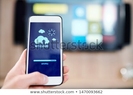 Smartphone with cloud and sun icons and uploading line on display Stock photo © pressmaster