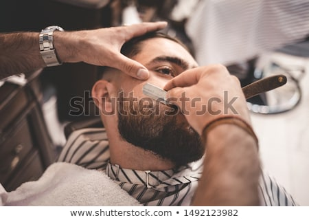 Fiatal férfi fodrász borotva visel baseballsapka Stock fotó © Kzenon