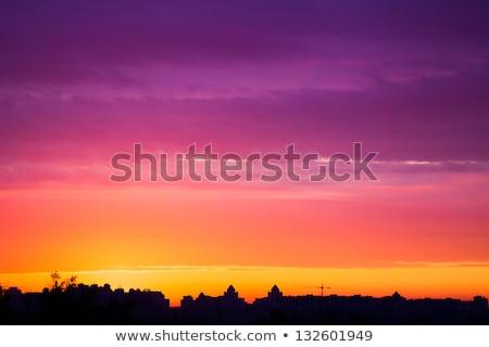 Dramatic sunset with orange sky and dark silhouettes of building Stock photo © vapi