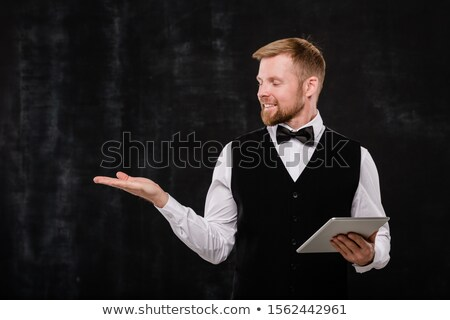 Young elegant waiter with touchpad looking at imaginary stuff on his hand Stock photo © pressmaster