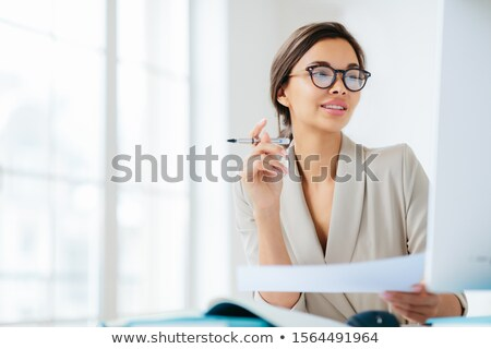 Prosperous businesswoman focused in monitor of computer, studies financial issues, holds document an Stock photo © vkstudio