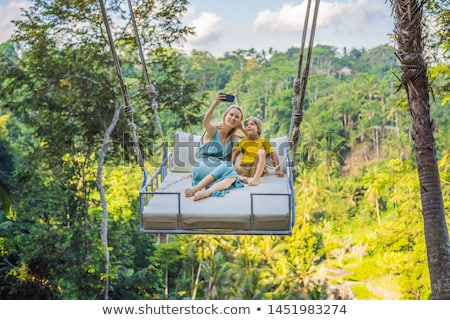 Young boy swinging in the jungle rainforest of Bali island, Indonesia. Swing in the tropics. Swings  Stock photo © galitskaya