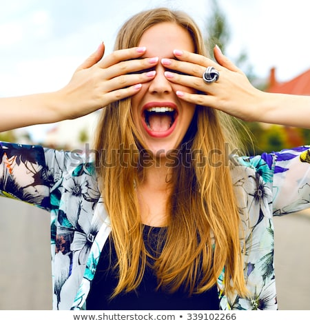 Image of young funny woman smiling and covering her eyes Stock photo © deandrobot