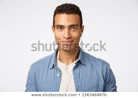 Handsome friendly, enthusiastic young macho man in blue shirt over t-shirt, listen music, place wire Stock photo © benzoix