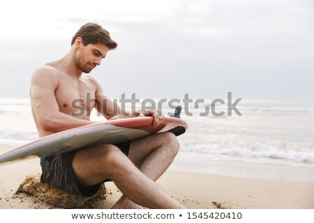 Bonito moço relaxante praia prancha de surfe homem Foto stock © deandrobot