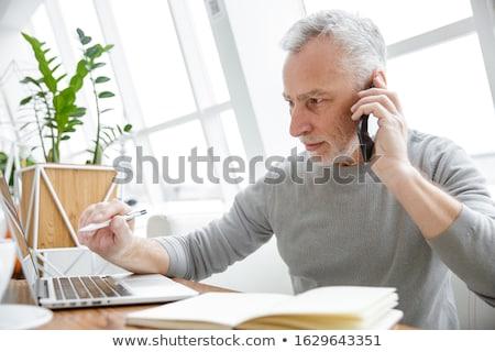 Fotoğraf odaklı olgun adam çalışma dizüstü bilgisayar cep telefonu Stok fotoğraf © deandrobot