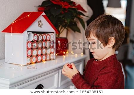 The boy opens a gift from the advent calendar Stock photo © galitskaya