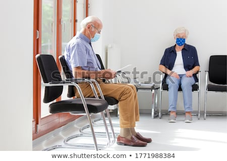 Coronavirus in the hospital covid 19. Woman in a medical mask Patients In Doctors Waiting Room Stock photo © galitskaya
