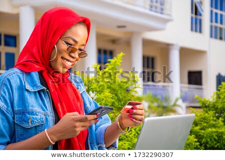 black woman using credit card and laptop outside stock photo © edbockstock