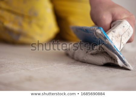 grouting tiles with rubber trowel man hand Stock photo © lunamarina