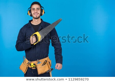 worker in blue overalls holding out ear protection Stock photo © photography33