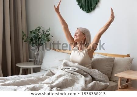 álmos nő nyújtás ágy fiatal nő otthon Stock fotó © wavebreak_media