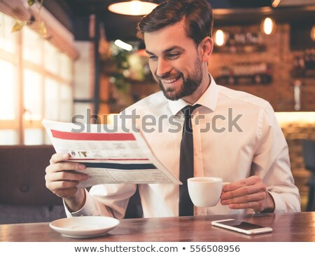 happy executive reading newspaper at cafe stock photo © stockyimages