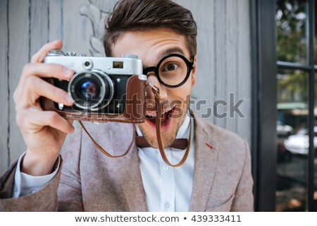Happy stylish nerd with camera outdoors Stock photo © deandrobot