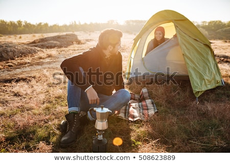 Young man making coffee for his girlfriend in a tent. Traveling together. Stock photo © deandrobot