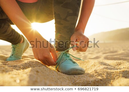 Running shoes - woman tying shoe laces on sandy beach at sunset Stock photo © vlad_star