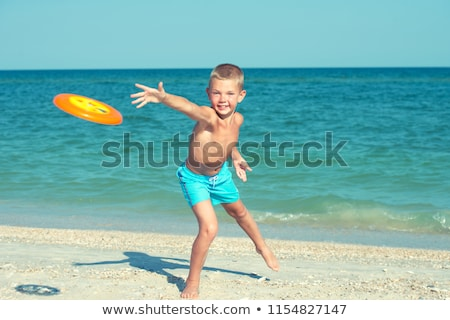 boy throwing frisbee on beach stock photo © is2