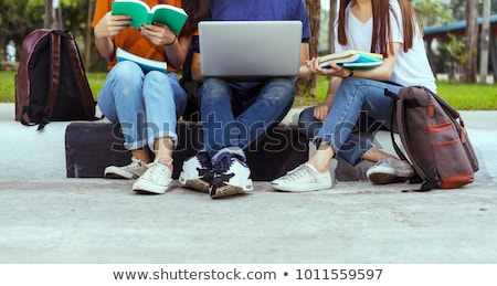 three happy students sitting with books laptop and bags stock photo © vlad_star