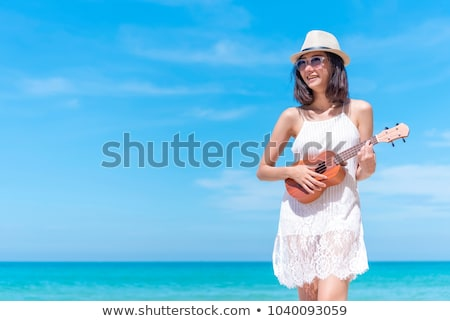 Pretty young woman with guitar on beach stock photo © Massonforstock