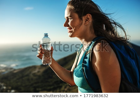side view of sports woman relaxing with bottle in hands stock photo © deandrobot