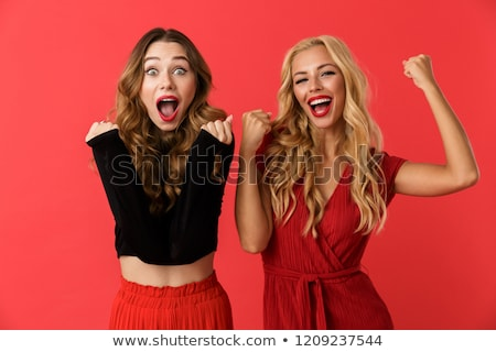 Excited young friends women standing isolated over red background showing winner gesture. Stock photo © deandrobot