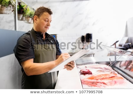 seller with clipboard selling seafood at fish shop Stock photo © dolgachov